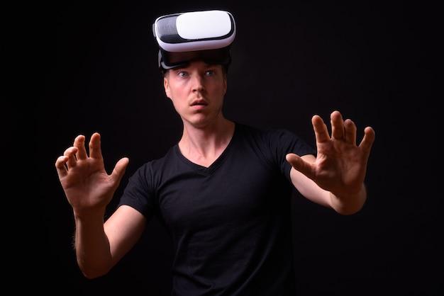 Portrait de jeune bel homme à l'aide d'un casque de réalité virtuelle et à la choqué