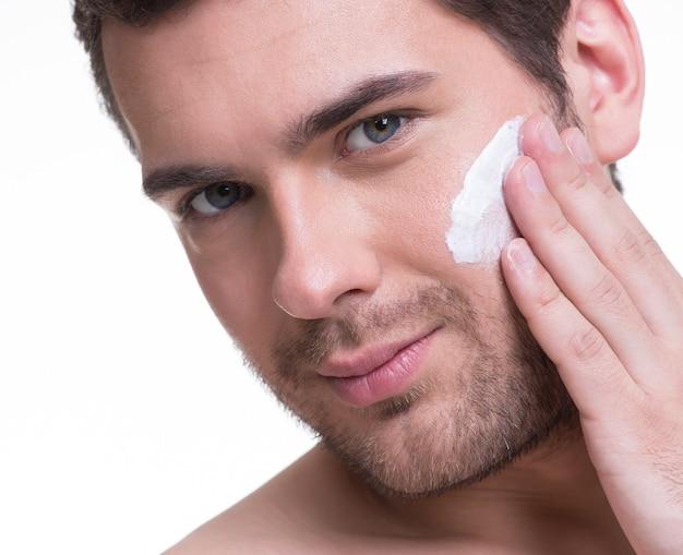 Portrait de jeune bel homme appliquant une lotion crème sur le visage - isolé sur blanc.