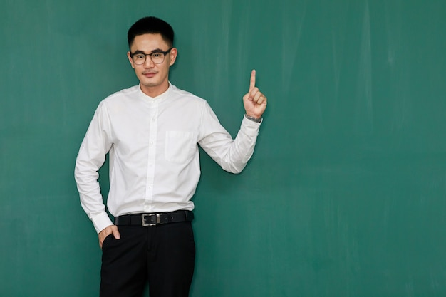 Portrait d'un jeune et bel homme asiatique portant des lunettes et des vêtements d'affaires décontractés, une chemise blanche et un pantalon noir, pose dans des gestes de publicité et présente des choses avec confiance en soi.