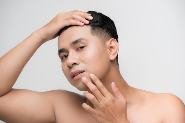 Portrait de jeune bel homme asiatique torse nu vérifiant son visage pour les soins de la peau et les concepts de beauté