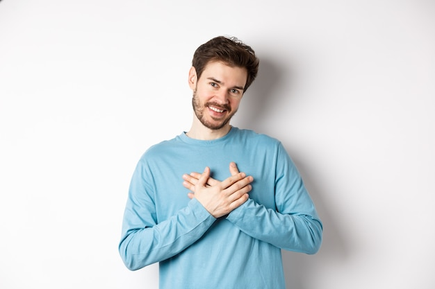 Portrait de jeune bel homme avec barbe, tenant les mains sur le cœur et disant merci, pensant à un moment agréable, debout sur fond blanc.