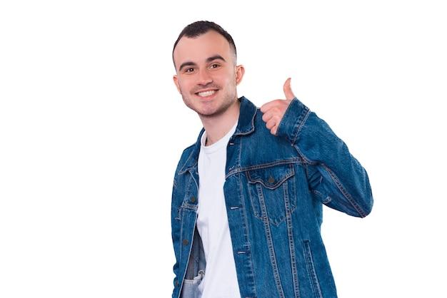 Portrait de jeune bel homme en blue-jeans montrant le pouce vers le haut et souriant