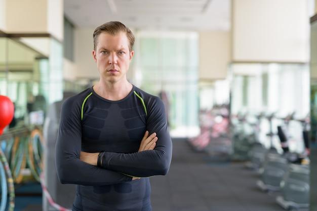 Portrait de jeune bel homme avec les bras croisés à la salle de sport pendant covid-19