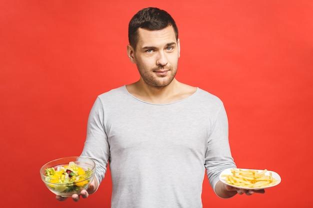 Portrait de jeune bel homme envie de malbouffe au lieu de manger des aliments sains
