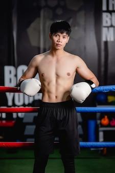 Portrait jeune bel homme en gants de boxe blancs pose debout sur toile dans une salle de sport, cours de boxe d'entraînement pour homme en bonne santé,