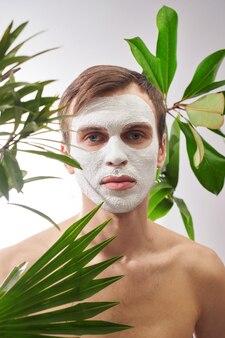 Portrait de jeune bel homme avec un masque cosmétique blanc sur son visage sur fond de plantes vertes. soins du visage pour hommes