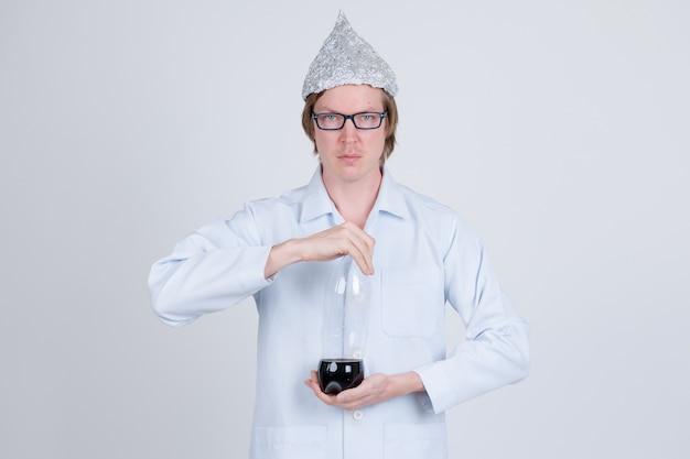 Portrait de jeune bel homme médecin portant chapeau de papier d'aluminium comme concept de théorie du complot sur blanc