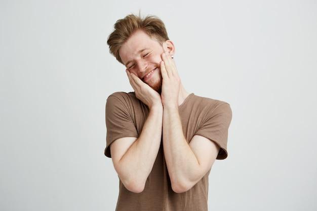 Portrait de jeune bel homme mignon souriant avec les mains sur les joues et les yeux fermés.