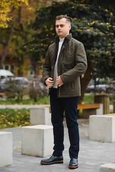 Portrait d'un jeune bel homme, modèle de mode, avec une coiffure moderne en milieu urbain, portant des vêtements décontractés.