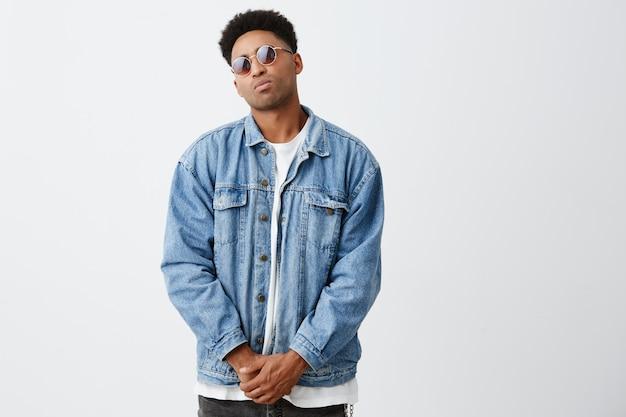 Portrait de jeune bel homme à la peau foncée avec une coiffure afro dans des vêtements à la mode décontractés et des lunettes de bronzage tenant par la main, posant dans une pose de sécurité, s'amusant