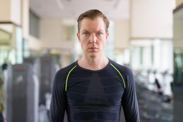 Portrait de jeune bel homme pensant à la salle de sport pendant covid-19