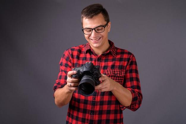 Portrait de jeune bel homme photographe tenant la caméra