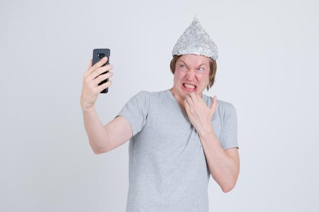 Portrait de jeune bel homme portant chapeau de papier d'aluminium comme concept de théorie du complot sur blanc