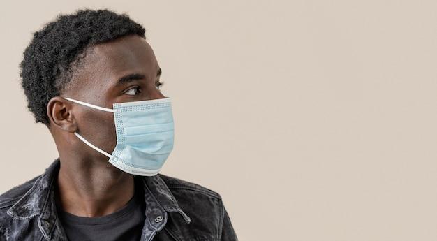 Portrait jeune bel homme posant avec masque