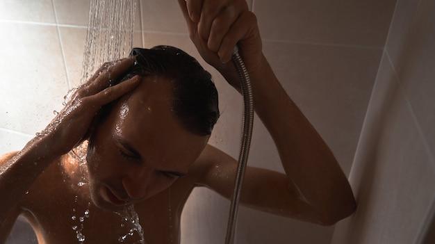 Portrait de jeune bel homme se lave avec du gel douche, mousse la tête avec du shampoing dans la salle de bain à la maison en gros plan