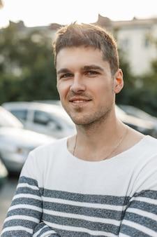 Portrait d'un jeune bel homme avec un sourire à l'extérieur