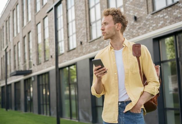 Portrait de jeune bel homme tenant un téléphone portable en attente de taxi à l'extérieur