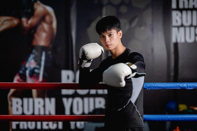 Portrait jeune bel homme en tenue de sport et gants de boxe blancs pose debout sur toile dans une salle de fitness, cours de boxe d'entraînement pour homme en bonne santé,