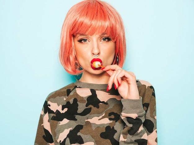 Portrait de jeune belle belle hipster mauvaise fille en short en jean à la mode et boucle d'oreille dans son nez ... modèle positif léchant des bonbons de sucre rond