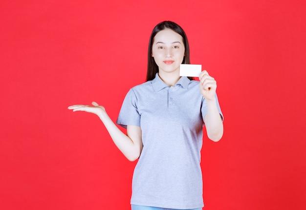 Portrait de jeune belle dame tenant la carte de visite et le côté droit de la main levée