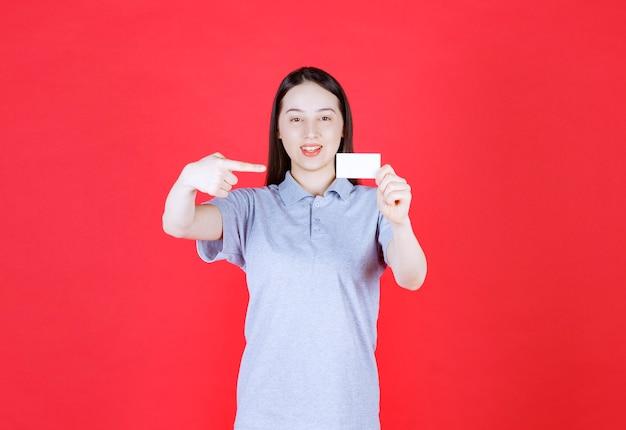 Portrait de jeune belle dame tenant une carte de visite et pointer le doigt dessus