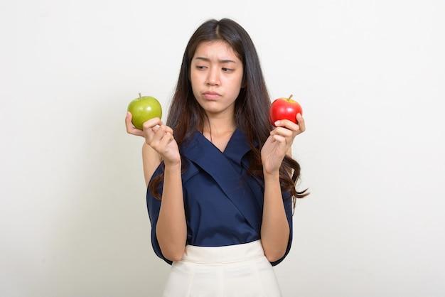 Portrait de jeune belle femme d'affaires asiatique en choisissant entre deux pommes