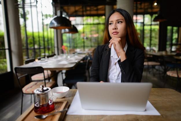 Portrait de jeune belle femme d'affaires asiatique travaillant au café