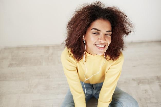 Portrait de jeune belle femme africaine dans les écouteurs souriant un clin de œil assis sur le plancher.