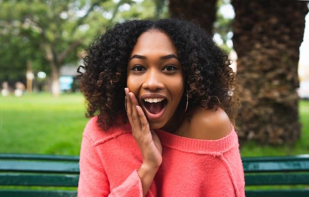 Portrait de jeune belle femme afro-américaine avec expression de surprise assis sur un banc dans le parc. en plein air.