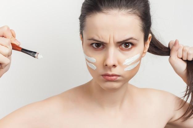 Portrait jeune belle femme appliquant un masque facial avec une brosse