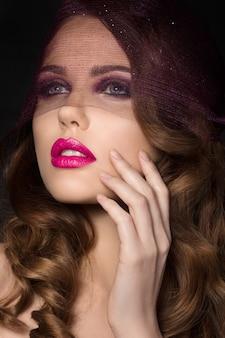 Portrait de jeune belle femme aristocratique avec des lèvres rose vif portant un voile violet et touchant son visage