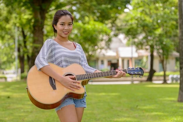 Portrait de jeune belle femme asiatique jouant de la guitare dans le parc en plein air