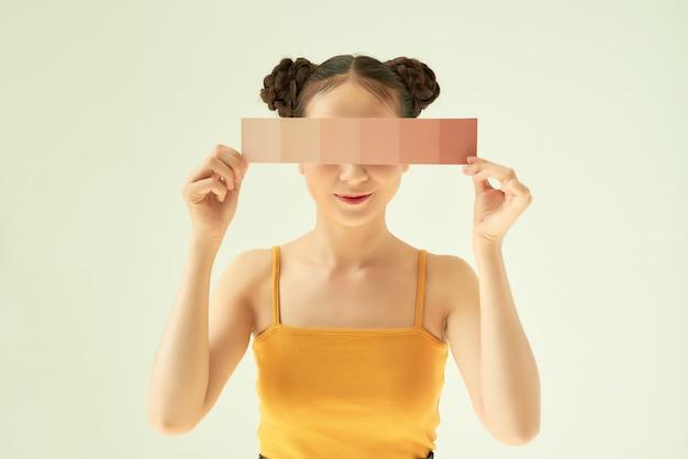 Portrait de jeune belle femme asiatique montrant la palette de couleurs de peau sur fond clair.