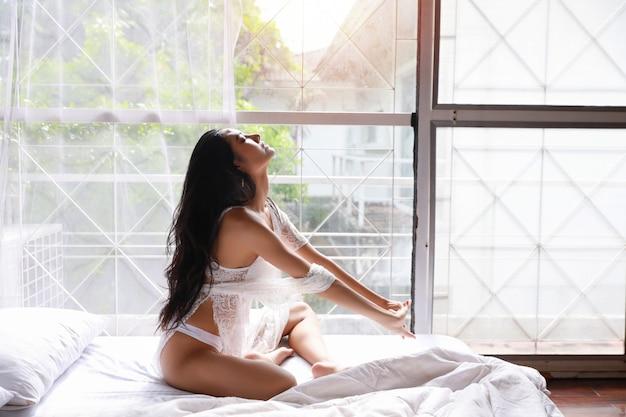 Portrait de jeune et belle femme asiatique portant des vêtements de nuit de lingerie blanche qui s'étend dans la chambre. jeune femme mignonne cheveux longs assis sur le lit et se réveille tard. concept de style de vie