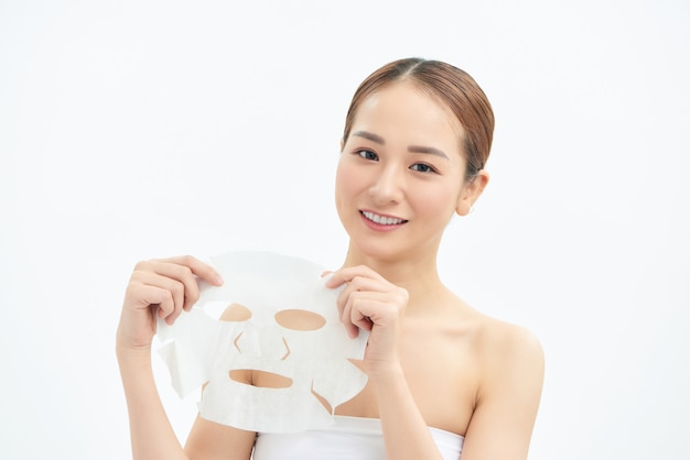 Portrait de jeune belle femme asiatique tenant un masque facial isolé sur fond blanc.
