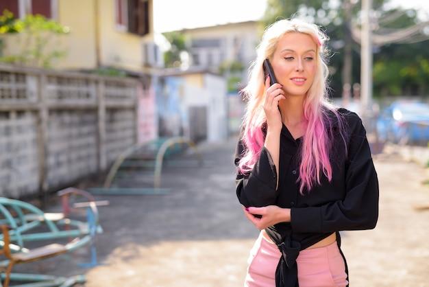 Portrait de jeune belle femme blonde à la découverte des rues de la ville à l'extérieur