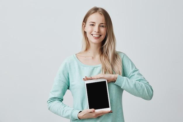 Portrait de jeune belle femme blonde souriante tenant et montrant une tablette numérique vierge