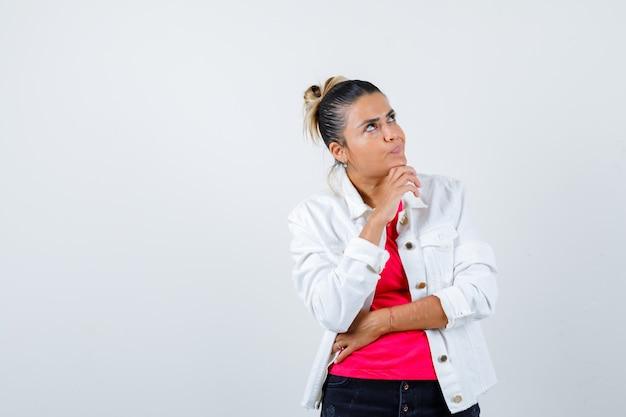 Portrait de jeune belle femme debout dans une pose de réflexion tout en levant les yeux en t-shirt, veste blanche et regardant perplexe vue de face