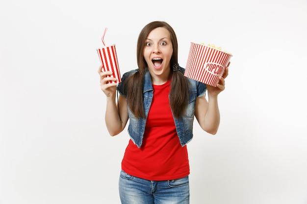 Portrait de jeune belle femme étonnée dans des vêtements décontractés en regardant un film, tenant un seau de pop-corn et une tasse en plastique de soda ou de cola isolé sur fond blanc. émotions dans le concept de cinéma.