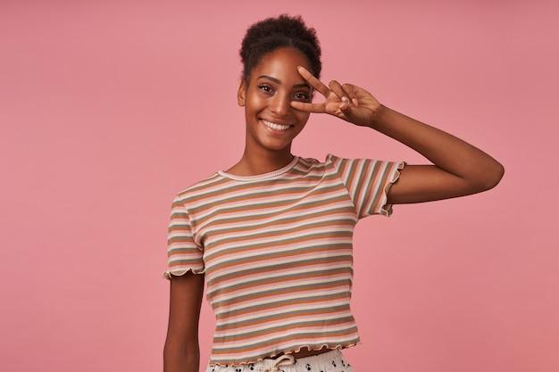 Portrait de jeune belle femme frisée aux cheveux bruns avec montrant le geste de la victoire et regardant joyeusement à l'avant avec un large sourire, posant sur un mur rose