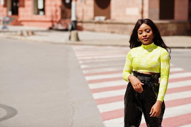 Portrait de jeune belle femme mannequin afro-américaine marchant sur un passage pour piétons, porter un haut vert et un pantalon noir brillant et mouillé.