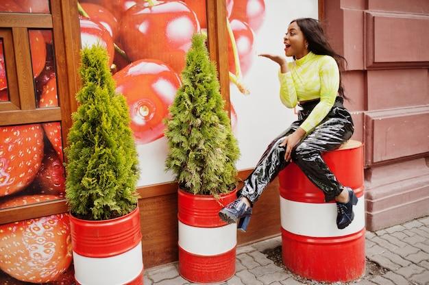 Portrait de jeune belle femme mannequin afro-américaine, porter en haut vert et pantalon noir brillant aspect mouillé, assis sur un baril rouge.