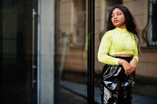 Portrait de jeune belle femme mannequin afro-américaine, porter en haut vert et pantalon noir brillant aspect mouillé.