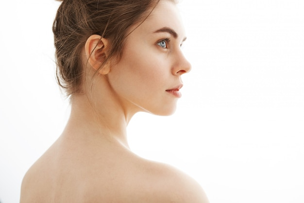 Portrait de jeune belle femme nue tendre avec chignon debout sur fond blanc.