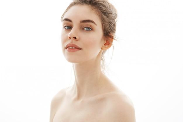 Portrait de jeune belle femme nue tendre avec chignon sur fond blanc.