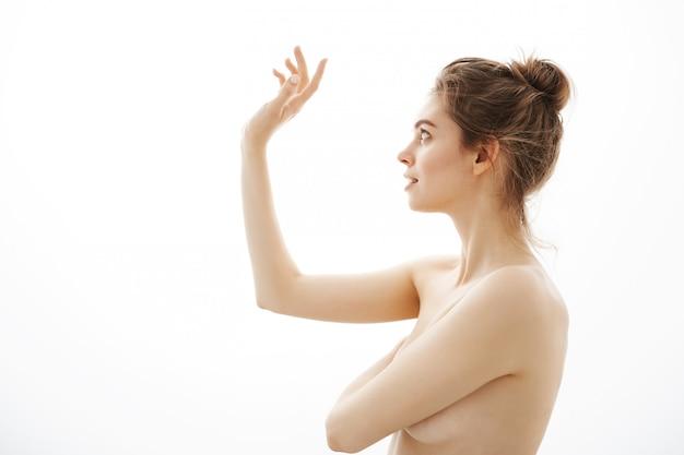 Portrait de jeune belle femme nue tendre avec chignon posant de profil sur fond blanc.