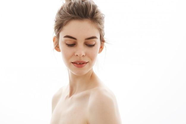 Portrait de jeune belle femme nue tendre avec chignon regardant vers le bas sur fond blanc.
