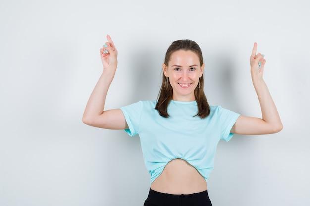 Portrait de jeune belle femme pointant vers le haut en t-shirt et regardant joyeuse vue de face