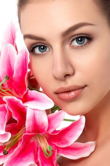 Portrait de jeune belle femme de race blanche avec des lys roses isolés sur blanc