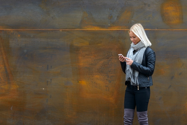 Portrait de jeune belle femme scandinave blonde contre le vieux mur de métal rouillé à l'extérieur